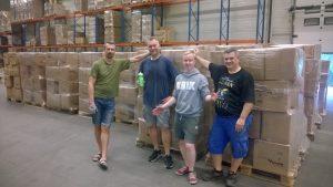 Fire menn oppstilt foran paller med esker i et lagerrom. Foto