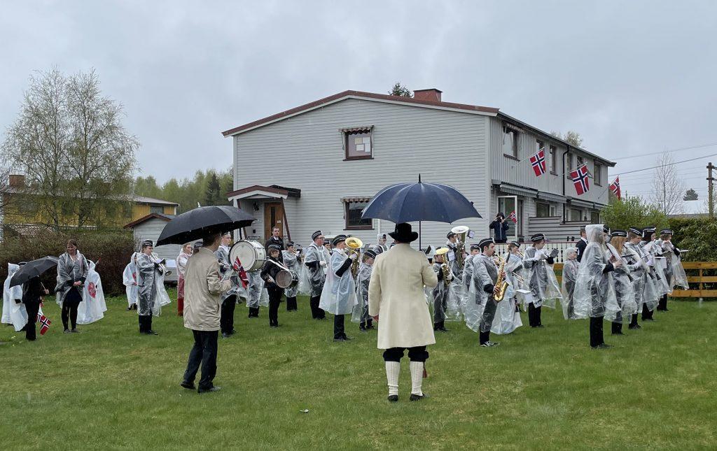 Jessheim skolekorps i regnponsjoer spiller marsj ved flaggstanga i Linjebo borettslag.